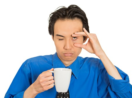Man drinking coffee and holding his eye open from fatigue
